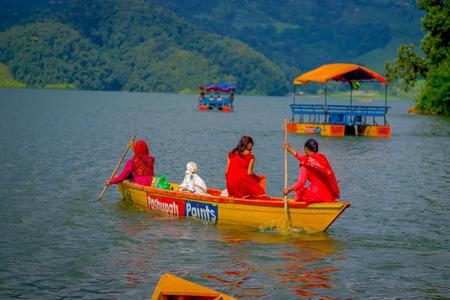 phewa: POKHARA, NEPAL - NOVEMBER 04, 2017:Gorgeous family enjoying of a beautiful day over a yellow boat at Begnas lake in Pokhara, Nepal. Editorial
