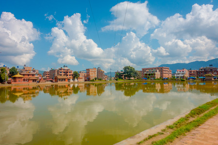 BHAKTAPUR, NEPAL - NOVEMBER 04, 2017: Close up of blurred traditional urban scene with an artificial pond of yellow water at Bhaktapur city, Nepal Editorial