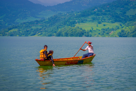 phewa: POKHARA, NEPAL - NOVEMBER 04, 2017: Unidentified couple enjoying the view with tourist guide paddling the boat in the Begnas lake in Pokhara, Nepal Editorial