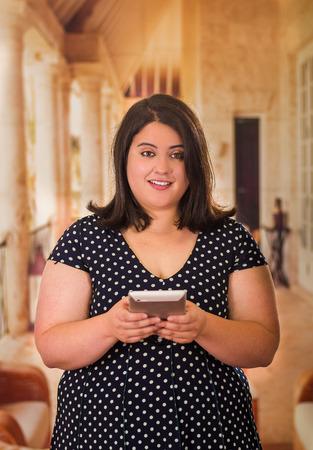 Schließen Sie oben von der schönen fetten Frau in einem schönen Kleid unter Verwendung ihrer Tablette in einem unscharfen Hintergrund Standard-Bild