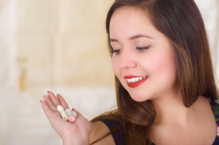 Portrait of a smiling woman holding in her hand a soft gelatin vaginal tablet or suppository, treatment of diseases of the reproductive organs of women and prevention of womens health Stock Photo
