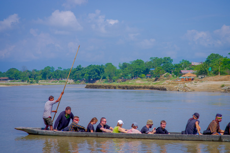 CHITWAN, NEPAL - NOVEMBER 03, 2017: Unidentified people canoeing safari on wooden boats Pirogues on the Rapti river, in Chitwan National Park, Nepal Redakční