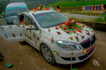 POKHARA, NEPAL OCTOBER 10, 2017: Beautiful car adorned with flowers and villagers celebrating a nepalese wedding in Besisahar, Nepa.
