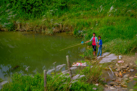 POKHARA, NEPAL - NOVEMBER 04, 2017: Unidentified children fishing in a pond in Pokhara, Nepal Editorial