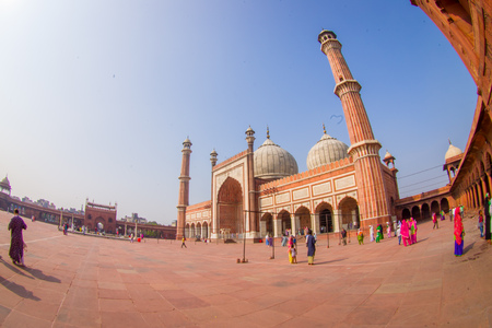 DELHI, INDIA - SEPTEMBER 27, 2017: Unidentified people walking in front of a beautiful Jama Masjid temple, this is the largest muslim mosque in India. Delhi, India, fish eye effect