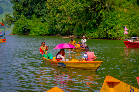 phewa: POKHARA, NEPAL - NOVEMBER 04, 2017: Unidentified group of people paddling the boats in the lake with at Begnas lake in Pokhara, Nepal.