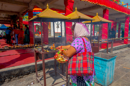 KATHMANDU, NEPAL - SEPTEMBER 04, 2017: Close up of unidentified woman at outdoors holding oblations inside of a basket near of Bindabasini temple, is of great religious importance to local Hindus. The temple itself is dedicated to the Hindu goddess Durga,