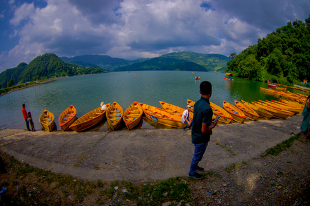 phewa: POKHARA, NEPAL - NOVEMBER 04, 2017: Unidentified people in the border of the lake with wooden boats in a row at Begnas lake in Pokhara, Nepal.