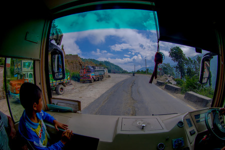 POKHARA, NEPAL OCTOBER 10, 2017: Close up of a little child with a bus driver in the cabain driving a truck on the road in the streets, located in Pokhara, Nepal.