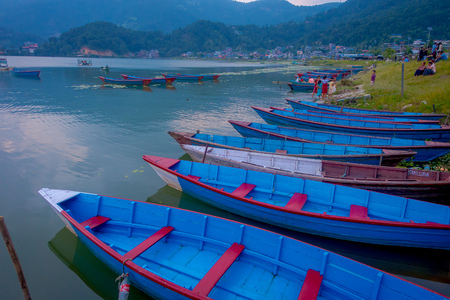 Pokhara, Nepal - September 04, 2017: Unidentified people sitting in a lakeshore enjoying the beautiful view of blue boats in the lake in Pokhara city , Nepal.