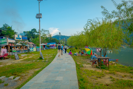 phewa: Pokhara, Nepal - September 04, 2017: Unidentified people wlaking in the stoned lakeshore with some food trucks seling food, in a beautiful day in Pokhara city , Nepal. Editorial