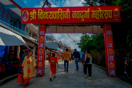 KATHMANDU, NEPAL - SEPTEMBER 04, 2017: Unidentified people walking in the morning market, under a red huge informative sign in Kathmandu, Nepal. The morning market is located near Annapurna temple at the center of Kathmandu, Nepal. Editorial
