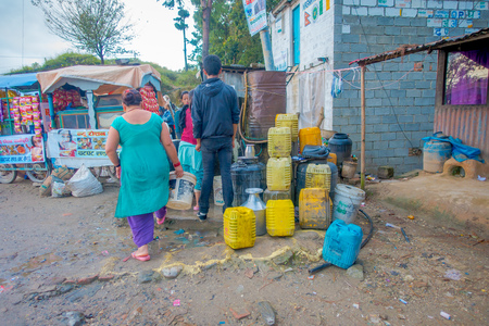 NAGARKOT, NEPAL OCTOBER 11, 2017: Unidentified woman walking at aoutdoors to fill with water some plastic trays in Nagarkot, Nepal. Editorial