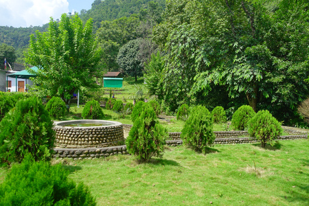 POKHARA, NEPAL OCTOBER 10, 2017: Beautiful garden in the enter of bat cave with a stoned structure in the middle of the jarden in Pokhara, Nepal