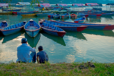 phewa: Pokhara, Nepal - September 04, 2017: Father and son sitting in the lakeshore enjoying the view of the boats in the lake in Pokhara city , Nepal