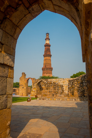 DELHI, INDIA - SEPTEMBER 25 2017: Beautiful view of Qutub Minar, through of a stoned arch, one of UNESCO world heritag site, built in the early 13th century located on south of Delhi, India