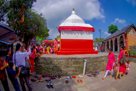 KATHMANDU, NEPAL - SEPTEMBER 04, 2017: Unidentified people giving oblations to a stoned white and red structure statues at outdoors near of of Bindabasini temple, is of great religious importance to local Hindus, fish eye effect