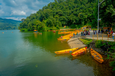 phewa: POKHARA, NEPAL - NOVEMBER 04, 2017: Unidentified people waiting to enjoy the ride in a beautiful and relaxing wooden yellow boat in a row at Begnas lake in Pokhara, Nepal Editorial