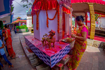 KATHMANDU, NEPAL - SEPTEMBER 04, 2017: Unidentified woman giving oblations to a stoned white structure with some golden statues at outdoors near of of Bindabasini temple, is of great religious importance to local Hindus, fish eye effect