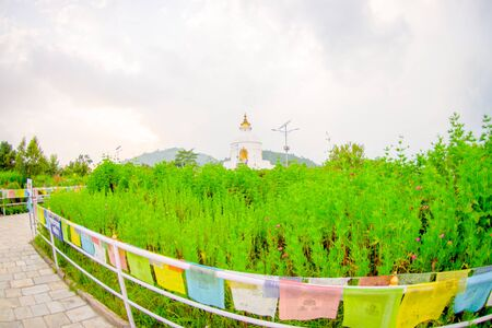POKHARA, NEPAL, SEPTEMBER 04, 2017: Close up of colorful fabrics with a description, with a beautiful brilliant-white World Peace Pagoda behind, in Pokhara is a massive Buddhist stupa, fish eye effect Editorial
