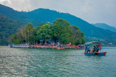 POKHARA, NEPAL - SEPTEMBER 04, 2017: Unidentified people enjoying a trip in a boat in the Phewa tal-lake with a island behind where is located the temple in Pokhara, Nepal
