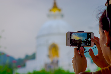 POKHARA, NEPAL, SEPTEMBER 04, 2017: Close up of a beautiful view of the temple in the screen of a smartphone with a blurred background of the brilliant-white World Peace Pagoda behind, in Pokhara is a massive Buddhist stupa, fish eye effect