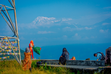 POKHARA, NEPAL, SEPTEMBER 04, 2017: Unidentified tourists at hilltop of the Sarangkot lookout point, holding flags and taking selfies in the mountain to view Annapurna Range during sunrise at Sarangkot, Nepal