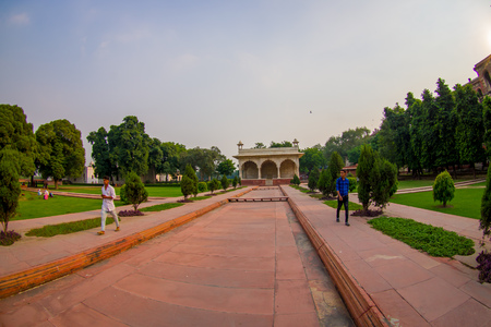 DELHI, INDIA - SEPTEMBER 25 2017: Unidentified man walking in a stoned path at outdoor of the Sawan or Bhadon Pavilion in Hayat Baksh Bagh of Red Fort at Delhi. Fish eye effect