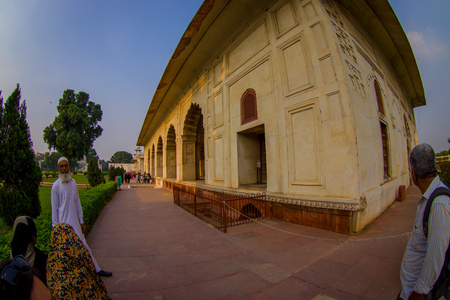 DELHI, INDIA - SEPTEMBER 25 2017: Unidentified old Indian man standing outside of Inlaid marble, columns and arches, Hall of Private Audience or Diwan I Khas at the Lal Qila or Red Fort in Delhi, India, fish eye effect