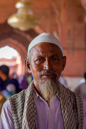 Delhi, India - September 27, 2017: Portrait of a man wearing a white indian hat, with a white beard looking at camera inside of the temple in Jama Masjid Mosque in Delhi, India in a blurred background Editorial