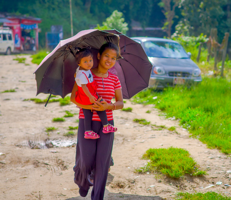 POKHARA, NEPAL - NOVEMBER 04, 2017: Unidentified woman holding a baby in her arms and protecting from the sun using a purple umbrella in Pokhara, Nepal. Editorial