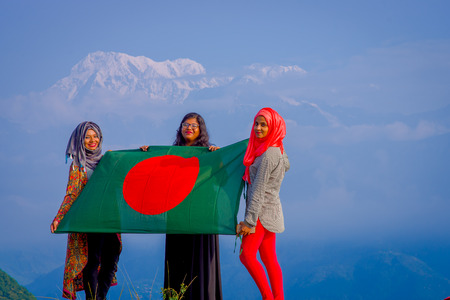 Pockhara, Nepal, September, 06 -2017: Close up of three beautiful nepalese women wearing a hijab and holding a a flag in their hands in a nature background