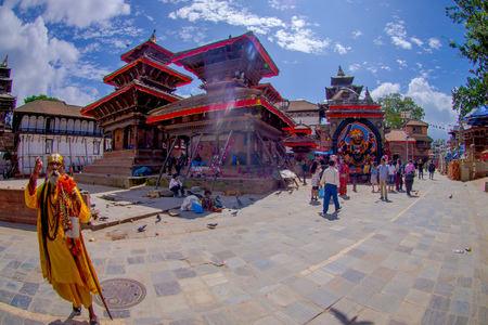 KATHMANDU, NEPAL OCTOBER 15, 2017: Unidentified people and sadhu budhist walking in a Durbar square in a beautidul sunny day near old hindu temples in Kathmandu, Nepal