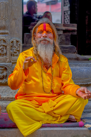 KATHMANDU, NEPAL OCTOBER 15, 2017: Close up of Shaiva sadhu with white beard, holy man in Pashupatinath Temple with painted face in Nepal Editorial