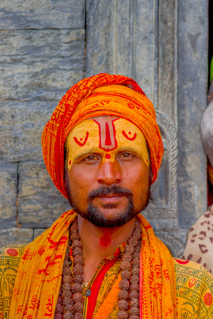 KATHMANDU, NEPAL OCTOBER 15, 2017: Portrait of young Shaiva sadhu, holy man in Pashupatinath Temple with painted face in Nepal