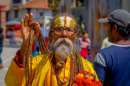KATHMANDU, NEPAL OCTOBER 15, 2017: Portrait of Nepalese sadhu man holding in his hands a prayer beads on the street of Kathmandu square in Nepal Editorial