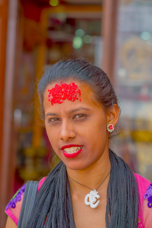 KATHMANDU, NEPAL OCTOBER 15, 2017: Portrait of women in traditional dress with red pieces of rice in her forehead, in Kathmandu, Nepal in a blurred background