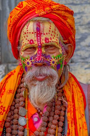 KATHMANDU, NEPAL OCTOBER 15, 2017: Portrait of Shaiva sadhu with white beard, holy man in Pashupatinath Temple with painted face, with prayer beads arounds his neck, in Nepal Editorial