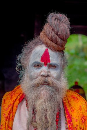 KATHMANDU, NEPAL OCTOBER 15, 2017: Portrait of Shaiva sadhu with white beard, holy man in Pashupatinath Temple with painted face in Nepal Editorial