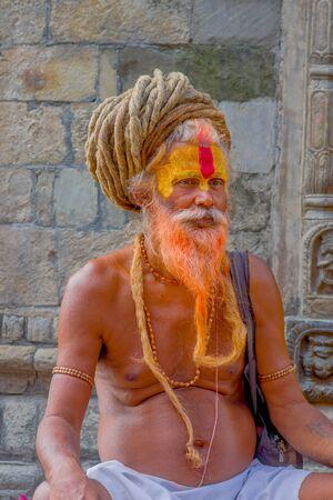 KATHMANDU, NEPAL OCTOBER 15, 2017: Close up of Shaiva sadhu with orange beard, holy man in Pashupatinath Temple with painted face in Nepal