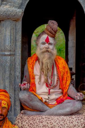 KATHMANDU, NEPAL - MARCH 22, 2017: Close up of Yogi Shaiva sadhu sitting in Pashupatinath Temple of Kathmandu with his legs crossed, in Nepal