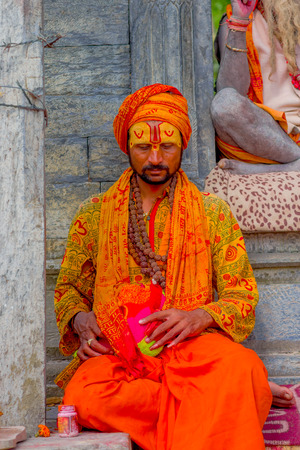 KATHMANDU, NEPAL OCTOBER 15, 2017: Close up of young Shaiva sadhu, holy man in Pashupatinath Temple with painted face in Nepal