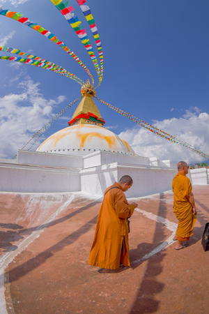 KATHMANDU, NEPAL OCTOBER 15, 2017: Close up of moks praying close the gorgeous monument Boudhanath stupa and its colorful flags in daylight with bue sky, following full restoration after 2015 earthquake damage. Kathmandu, Nepal, fish eye effect