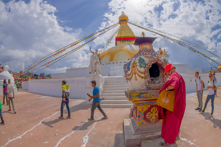 KATHMANDU, NEPAL OCTOBER 15, 2017: Unidentified people walking at outdoors close to the monument Boudhanath stupa and its colorful flags in daylight with bue sky, in Kathmandu, Nepal Editorial