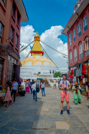 KATHMANDU, NEPAL OCTOBER 15, 2017: Unidentified people walking in the streets between some buildings and enjoying the beautiful monument of Boudhanath stupa and its colorful flags in daylight with bue sky, in Kathmandu, Nepal.