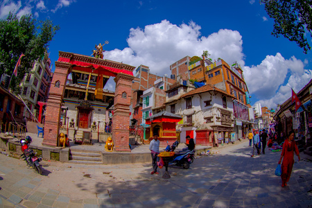 KATHMANDU, NEPAL OCTOBER 15, 2017: Unidentified people walking in the streets of the town with some buildings in reconstruction after the earthquake in 2015 of Durbar square in Kathmandu, capital of Nepal. Editorial