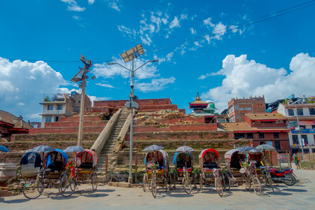 KATHMANDU, NEPAL OCTOBER 15, 2017: Rickshaws parked in empy Durbar square with some tourists near the old Indian temples in Katmandu. Editorial