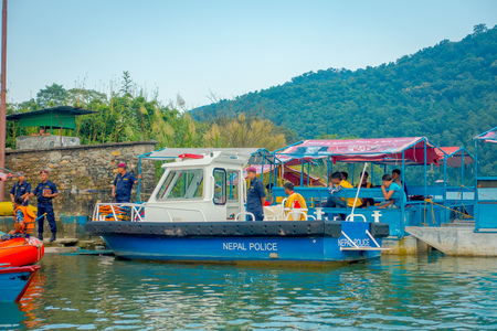 phewa: POKHARA, NEPAL - SEPTEMBER 04, 2017: Unidentified people in the lakeshore at outdoor view with many boats and police boat parked in a row in the Phewa tal-lake in Pokhara, Nepal Editorial