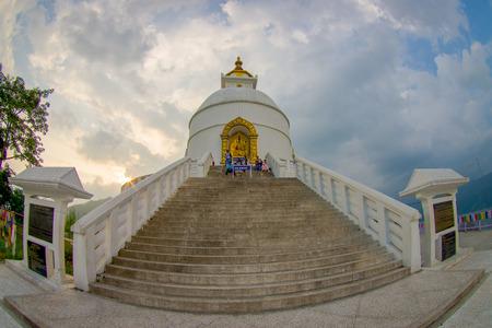 phewa: POKHARA, NEPAL, SEPTEMBER 04, 2017: Balanced on a narrow ridge high above Phewa Tal, the brilliant-white World Peace Pagoda in Pokhara is a massive Buddhist stupa