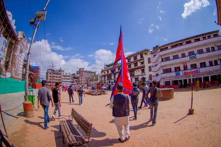 KATHMANDU, NEPAL OCTOBER 15, 2017: Unidentified people walking in the streets and a nepalese man holding a flag in his hands in Durbar square in Kathmandu, capital of Nepal, fish eye effect.